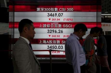Pessoas passam por painel com índices do mercado acionário chinês em Hong Kong.   REUTERS/Bobby Yip