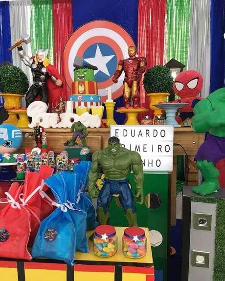 61. Ideias para festa dos Vingadores decorara com bonecos e painel com escudo do Capitão América – Foto: Peritus Festas