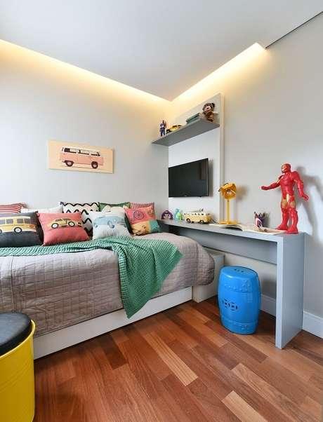 6. Quarto com escrivaninha planejada e piso laminado. Projeto por Tetriz Arquitetura e Interiores
