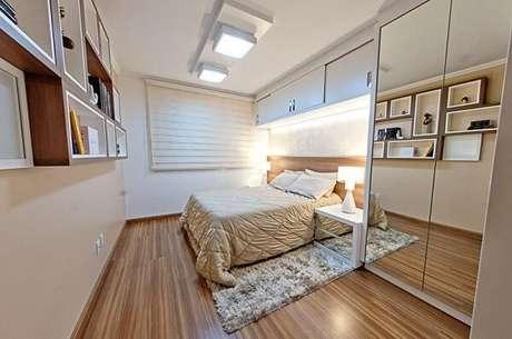 4. Quarto de casal com armário espelhado embutido e piso laminado. Projeto por Camila Chalon
