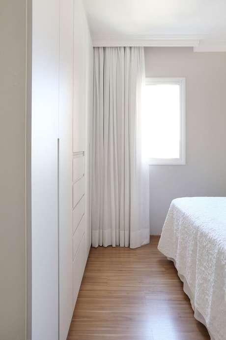 60. Quarto de casal com decoração clean conta com guarda roupa branco e piso laminado. Projeto por Livia Dalmaso