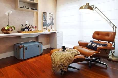65. Sala de leitura com poltrona confortável e piso de madeira laminado. Projeto por Serra Vaz Arquitetura
