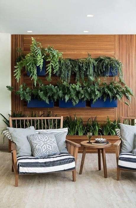 15. Cadeiras para varanda decorada com revestimento de madeira e jardim vertical – Foto: Estreno Casa