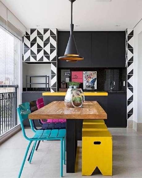 20. Cadeiras coloridas para varanda gourmet decorada com pendentes pretos e churrasqueira – Foto: Pinterest