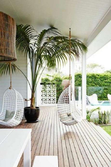21. Cadeiras de balanço para varanda decorada com grande vaso de planta e piso de madeira – Foto: OneChitecture