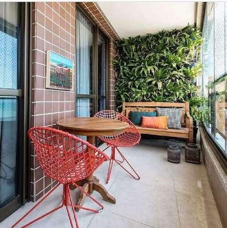 23. Cadeiras para varanda de apartamento decorado com jardim vertical e mesa de madeira – Foto: Dicas Decor