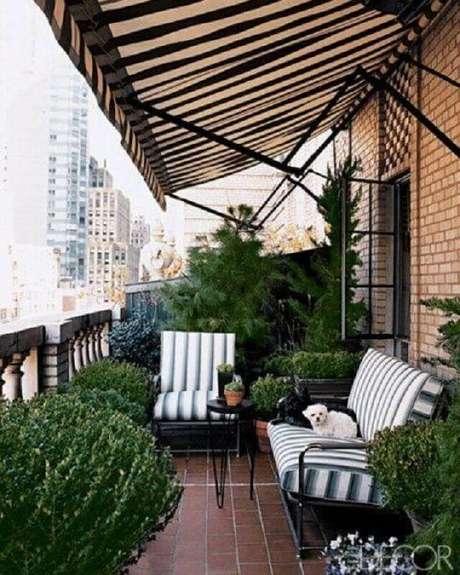 39. Jogo de cadeiras para varanda decorada com vários vasos de plantas – Foto: Design Maze