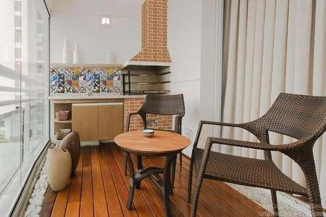 43. Jogo de cadeiras para varanda pequena com churrasqueira e mesa redonda de madeira – Foto: Caroline Manfrin