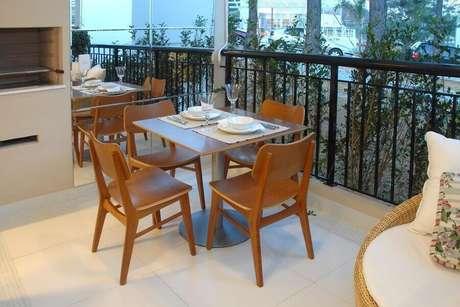 47. Jogo de mesa e cadeira para varanda moderna com churrasqueira e parede espelhada – Foto: Teresinha Nigri