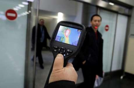 Agente do serviço sanitário epidemiológico usa scanner térmico para detectar sinal de febre em passageiros que chegam da China no aeroporto de Almaty, no Cazaquistão 21/01/2020 REUTERS/Pavel Mikheyev