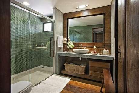 12. Banheiro de apartamento decorado com revestimento de madeira e pastilhas verdes para área do box – Foto: Gislene Lopes