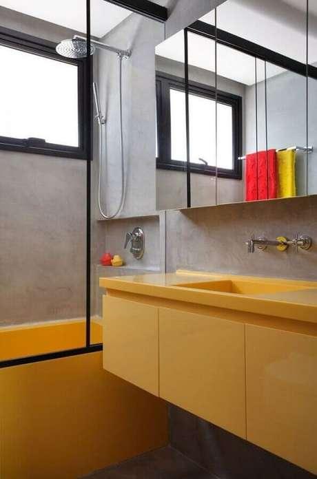 16. Modelo de banheiro de apartamento moderno com paredes de cimento queimado e banheira e gabinete amarelos – Foto: Archdaily