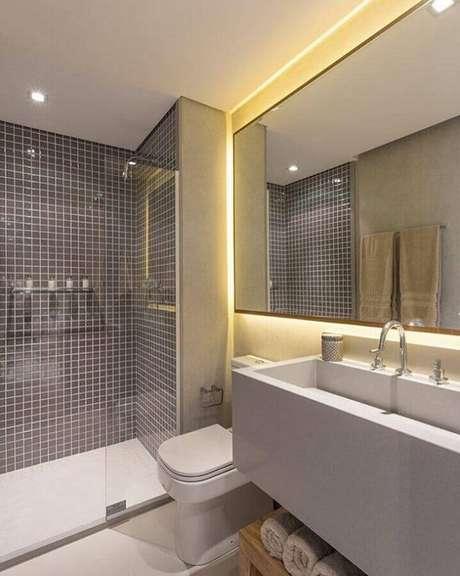 17. Banheiro de apartamento moderno todo cinza decorado com pastilha na área do box e iluminação embutida – Foto: Sesso & Dalanezi Arquitetura