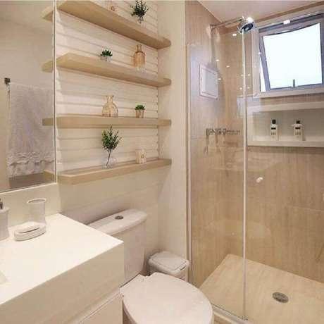 26. Decoração em tons neutros para banheiro de apartamento pequeno com prateleiras de madeira para decoração – Foto: Mônise Rosa