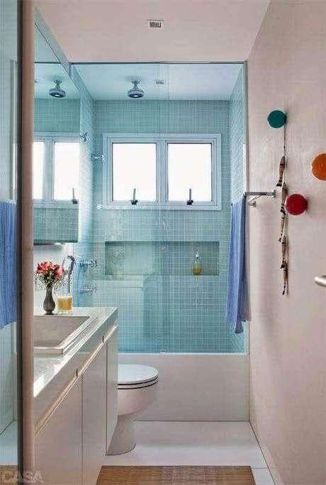 29. Banheiro de apartamento pequeno decorado simples com pastilhas azuis na área do box – Foto: Casa Perferies
