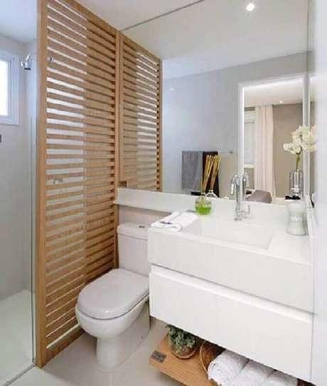 30. A divisória de madeira deu um toque acolhedor para a decoração de banheiro de apartamento todo branco – Foto: D+ Arquitetura