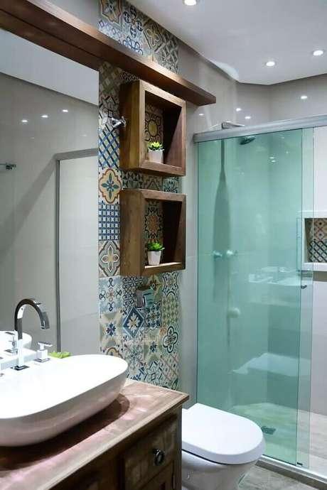 37. Decoração de banheiro de apartamento com azulejo hidráulico e nichos de madeira – Foto: Assetproject