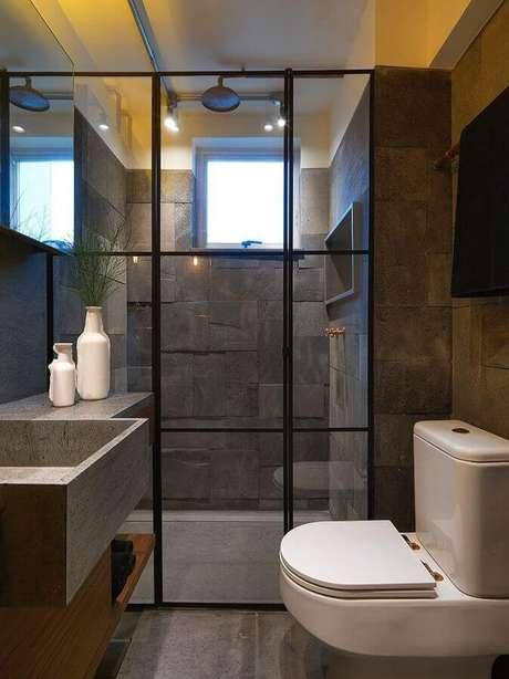 39. É importante investir em uma boa iluminação para banheiro pequeno de apartamento com revestimento escuro – Foto: Studio Marcio Michaluá