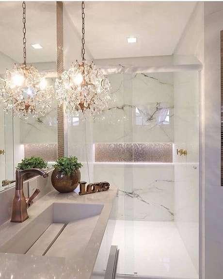 9. Decoração para banheiro de apartamento de luxo com lustre de cristal e mármore branco – Foto: Pinterest