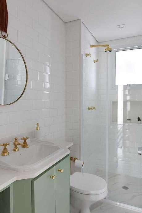 42. Decoração retrô para banheiro de apartamento com gabinete verde e torneiras douradas – Foto: Webcomunica