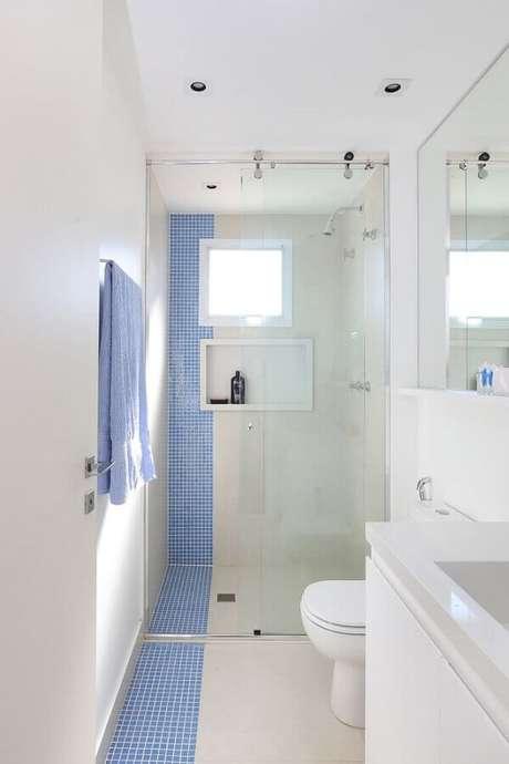 43. Decoração simples para banheiro pequeno de apartamento com faixa de pastilhas azuis – Foto: Jeito de Casa