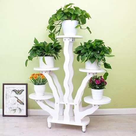 2. Floreira de madeira branca sustenta cinco flores em sua estrutura. Fonte: Pinterest