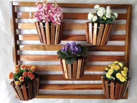 35. Floreira de madeira sustenta cinco vasos de flores. Fonte: Pinterest