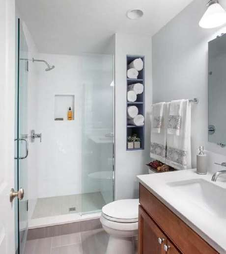 47. Modelo de banheiro de apartamento simples com nichos embutidos e gabinete de madeira – Foto: Pinterest