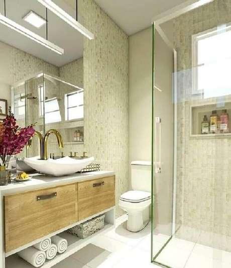 48. Decoração para banheiro de apartamento com armário suspenso e torneira dourada – Foto: ArqA2 Arquitetura & Interiores