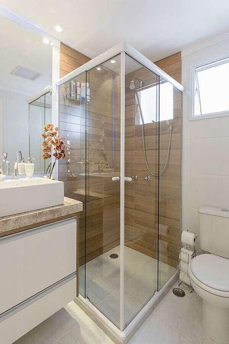 49. Modelo de banheiro de apartamento decorado com porcelanato que imita madeira na área do box – Foto: LO Interiores