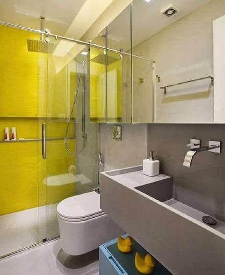 52. Decoração para banheiro de apartamento moderno com revestimento amarelo na área do box e bancada cinza – Foto: Roberta Devisate
