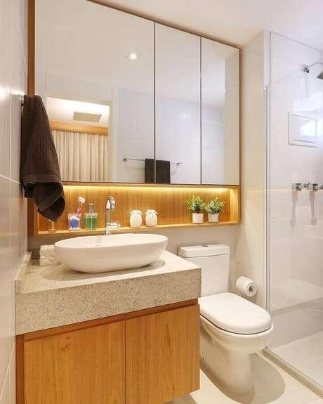 54. Modelo de banheiro de apartamento planejado com armário de madeira e iluminação embutida – Foto: Webcomunica