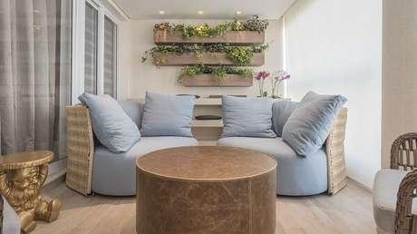 6. Varanda com sofá em tons neutros, mesa de canto dourada e floreira de madeira. Projeto por Marli Assis