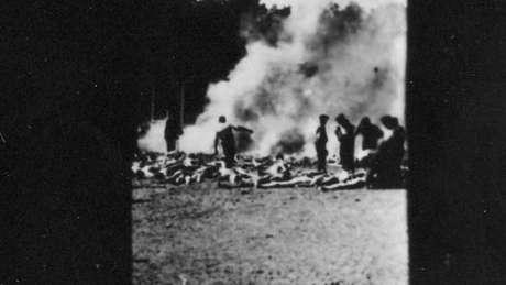 Outra foto clandestina mostra a cremação de corpos em uma vala aberta