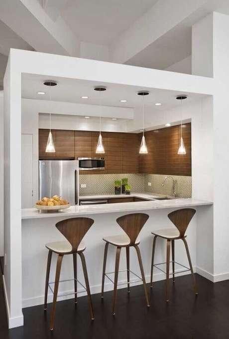 38. Banquetas modernas de madeira para cozinha americana pequena toda branca com revestimento de madeira – Foto: Decoração e Projetos
