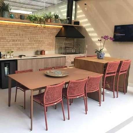 14. Varanda gourmet com churrasqueira decorada com parede de tijolinho e cadeiras cor terracota – Foto: Webcomunica