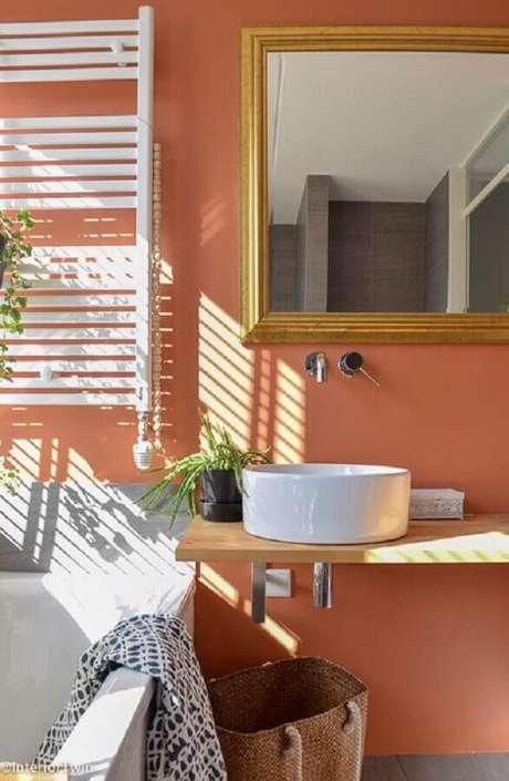 17. Cor de parede terracota para decoração de banheiro com bancada de madeira – Foto: InteriorTwin