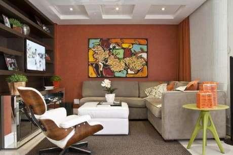 21. Sala de estar decorada com cor de parede terracota e sofá de canto cinza – Foto: Arquitetando