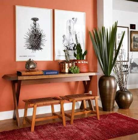 3. Hall de entrada decorado com cor de parede terracota e aparador de madeira – Foto: Pinterest