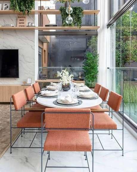 33. Casa ampla e moderna decorada com paredes de vidro e mesa de jantar com cadeiras na cor terracota – Foto: Triplex Arquitetura
