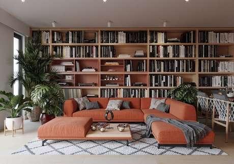 34. Decoração moderna na cor terracota para sala de estar com estante planejada em parede inteira – Foto: Behance