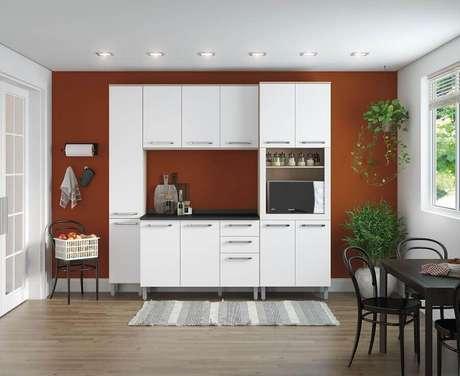 35. Decoração simples para cozinha com parede na cor de tinta terracota e armário branco – Foto: Webcomunica