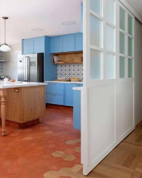 39. Piso na cor terracota para decoração de cozinha planejada com armários azuis – Foto: Pinterest