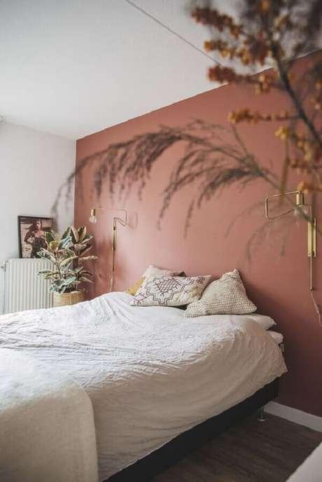 42. Quarto de casal minimalista decorado na cor de parede terracota e com vasos de plantas – Foto: Pinterest