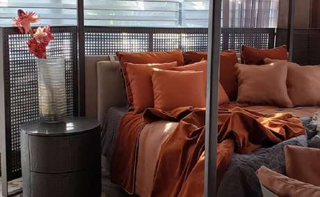 43. Quarto moderno todo cinza decorado com almofadas e roupa de cama na cor terracota – Foto: Behance