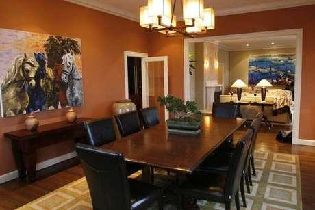 45. Sala de jantar decorada com cor de tinta terracota e mesa de madeira – Foto: Pinterest