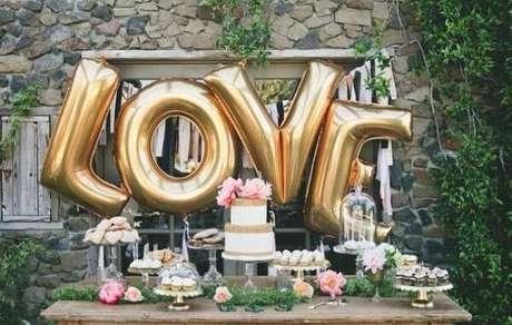 70- Balões metálicos na mesa do bolo transforma a decoração de noivado. Fonte: Planejando Meu Casamento