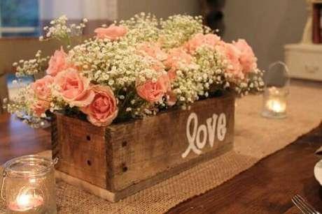 19- Na decoração de noivado a caixinha de flores com castiçais de velas proporcionam um toque delicado ao ambiente. Fonte: Casar é um Barato