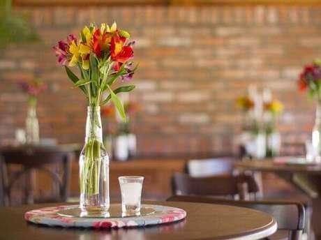 21- Uma decoração de noivado simples pode ser realizada com garrafas e flores sobre as mesas. Fonte: Inesquecível Casamento