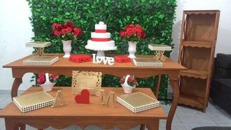 68- Decoração de noivado simples com vasos de flores vermelhas combinando com o laço do bolo. Fonte: Pinterest